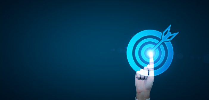 A hand in a suit touching the center of a picture of a target which gets blue. Dark blue background. Concept of achieving a goal.